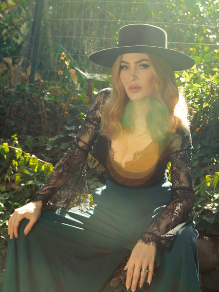 Sitting in her sunny garden, Micheline Pitt models the La Sorcière Top in Black from La Femme en Noir.