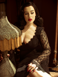 Posing next to a vintage era lamp, Rachel edory shows off the La Sorcière Top in Black from gothic vintage clothing maker La Femme en Noir.