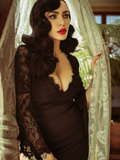 Micheline Pitt wearing the La Sorcière Top in Black while wrapped in white lace curtains.