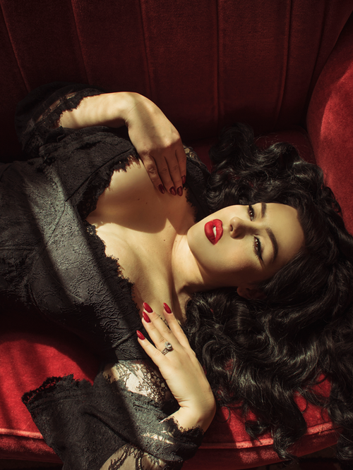 Laying down on a red velvet couch, Rachel Sedory wears the sultry La Sorcière Top in Black from La Femme en Noir.