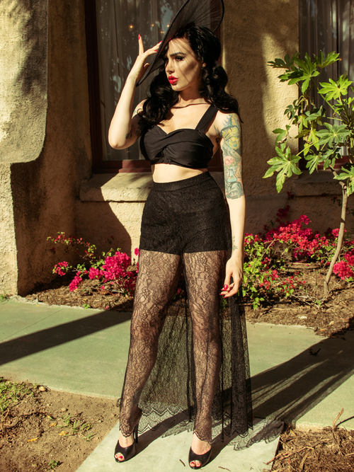 Micheline Pitt modeling the Black Widow Palazzo Pants in Black Lace with a black top and matching sunhat.