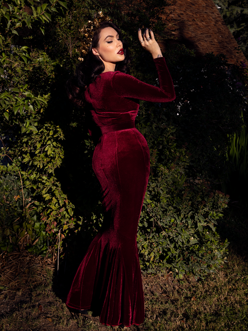 A back shot of Micheline Pitt in a lush garden looking into the sunlight while modeling the Black Marilyn gown in oxblood.