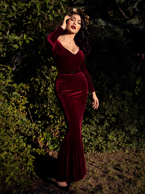 A full length photo of Micheline Pitt in a lush garden looking into the sunlight while modeling the Black Marilyn gown in oxblood.