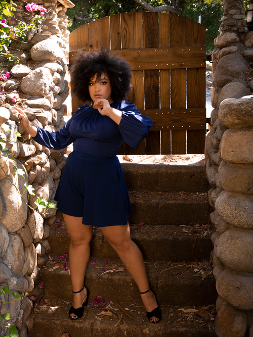 A full length photo of Ashleeta standing in front of a wooden gate while modeling the Black Widow Tap Shorts in Navy.