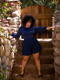 Ashleeta stands in front of a wooden gate while modeling the Black Widow tap shorts in Navy by La Femme En Noir.