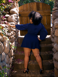 A back shot of Ashleeta, standing on stairs, modeling the Black Widow Tap Shorts in Navy.