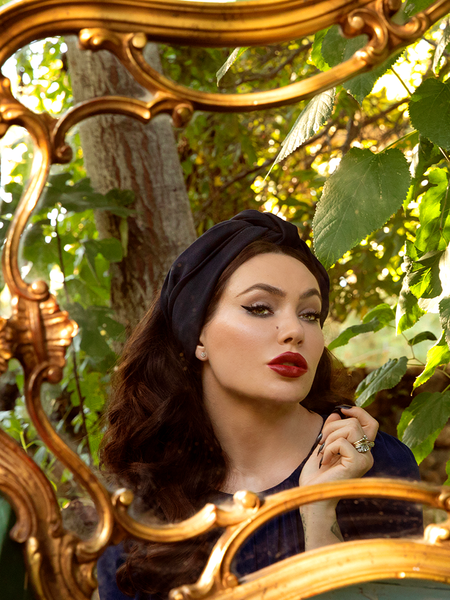 Micheline Pitt gazing into a gold plated mirror wearing the Art Deco Head Scarf in Navy Ponte.