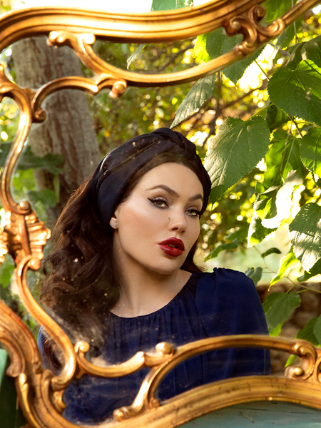Gazing longingly into a gold-plated mirror, Micheline Pitt rocks a blue, flowy top with Art Deco Head Scarf in Navy Ponte.