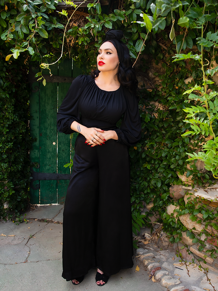 Micheline Pitt staring off into the distance off camera, wearing the Opera Satin Palazzo Pants from La Femme en Noir.