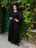 Posing with her hands on her hands and looking to the side of the camera, models an all black outfit including flowy long sleeve shirt, black headwrap and black Opera Satin Palazzo Pants.