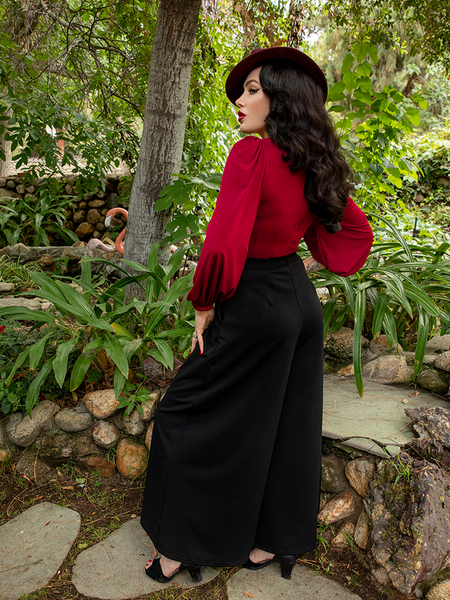 Micheline Pitt slightly turned to the side while wearing the Opera Satin Palazzo Pants from La Femme en Noir - a gothic style clothing company.