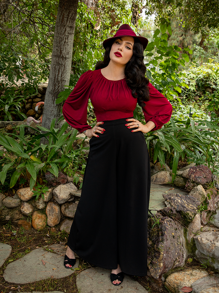 Stood in a garden  and posing with her hands on her hips, Micheline Pitt wears the black Opera Satin Palazzo Pants from La Femme en Noir.
