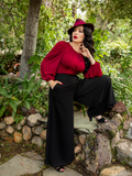 Micheline Pitt in a blood red flowing top, wears the Opera Satin Palazzo Pants from La Femme en Noir.