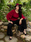 Sitting on stones in a lush garden setting, Micheline Pitt models the Opera Satin Palazzo Pants from La Femme en Noir.