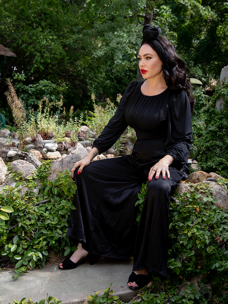 Sat amongst stones in a vibrant and lush garden, Micheline Pitt shows off the goth inspired Opera Satin Palazzo Pants from La Femme en Noir.