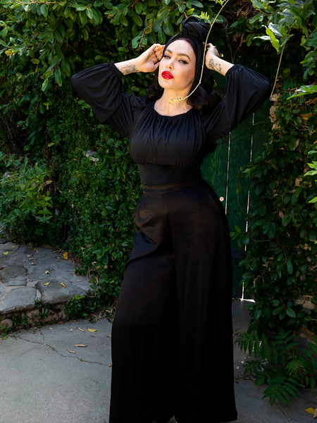 Micheline Pitt in an all black outfit - flowy, long-sleeve black top, black headwrap and Opera Satin Palazzo Pants.