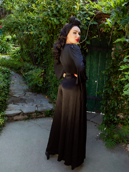 Shot in a garden setting in front a hunter green wooden door, Micheline Pitt looks over her shoulder back at the camera while showing off the back of the Opera Satin Palazzo Pants.