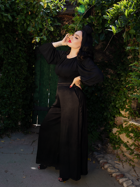 Micheline Pitt, posed so that we can see her profile, stands with a black, flowy top on along with the goth stlye Opera Satin Palazzo Pants from La Femme en Noir.
