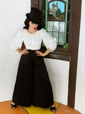 Micheline Pitt posed in a standing position while wearing the Opera Satin Palazzo Pants - gothic style clothing from La Femme en Noir.