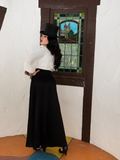 Micheline Pitt showing off the back of the gothic style outfit she's wearing featuring the Opera Satin Palazzo Pants.