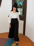 Walking towards the camera, Micheline Pitt shows off the Opera Satin Palazzo Pants.