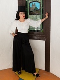 In her goth vintage outfit, Micheline Pitt looks off-camera while wearing the Opera Satin Palazzo Pants, white flowy top and black tophat.