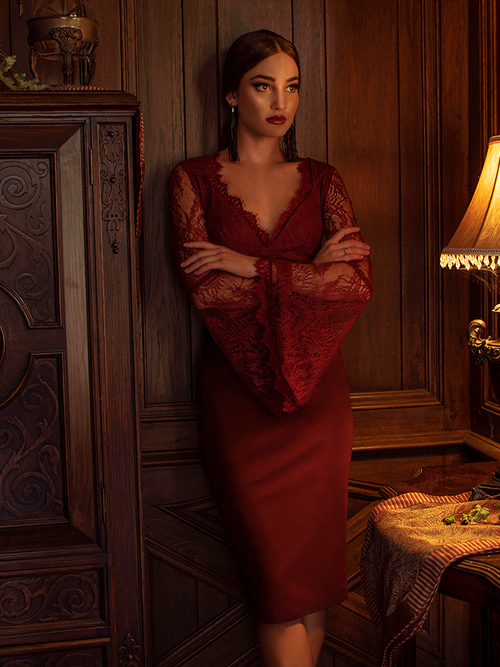 Aliza standing in a dimly lit room with her arms crossed modeling the Vamp pencil skirt in oxblood.