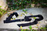 Gothic retro clothing company La Femme en Noir's Serpentine Infinity Buckle in Antique Silver resting on the ground.