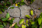 Photographed among leaves and dead branches, the Serpentine Choker in Antique Silver radiates a brilliant shine.