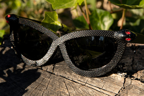 Close up shot of the Serpent Sunglasses in Black from La Femme en Noir sitting on top of a old, wooden log.
