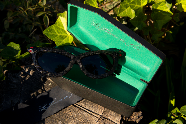 The Serpent Sunglasses in Black sitting on top of the opened coffin-shaped carrying case along with branded cleaning cloth.