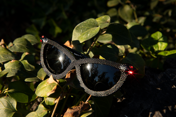 The red ruby of the snakes eye glistens on the Serpent Sunglasses in Black from La Femme en Noir.