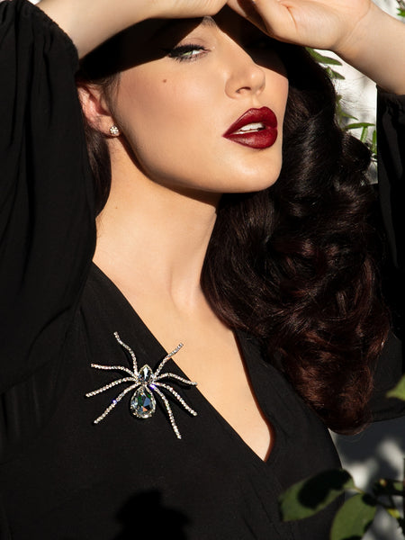 Micheline Pitt wearing a black top adorned the the Black Widow Rhinestone Spider Brooch.