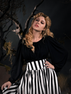 Linda standing in a goth graveyard in a gothic top wearing a black and white stripe skirt.