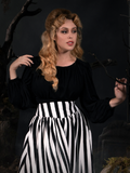 Linda photographed in her gothic retro outfit featuring a black and white striped skirt and black goth top.