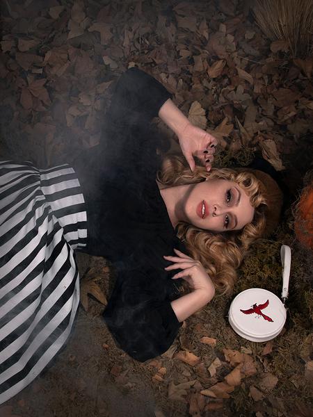 Linda laying on the leaf covered ground wearing the Salem Top in Black.