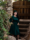 Micheline Pitt standing in a mossy garden in front of a wooden gate modeling the Salem Dress in Hunter Green.