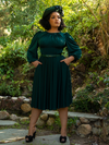 Model Ashleeta showing off the pockets on her Salem Dress in Hunter Green while posing in a garden.