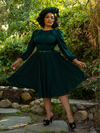 Full length photo of Ashleeta in the Salem Dress in Hunter Green from gothic retro clothing maker La Femme en Noir.