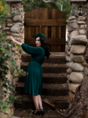 Micheline Pitt turned away from the camera but glancing back at it while wearing the Salem Dress in Hunter Green.