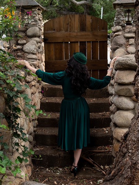 In a garden setting Micheline Pitt walks away from the camera while wearing the Salem Dress in Hunter Green.