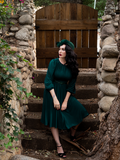 Micheline Pitt looking away while wearing the Salem Dress in Hunter Green.