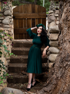 Micheline Pitt standing in a rustic garden setting in her gothic retro style dress from La Femme en Noir.