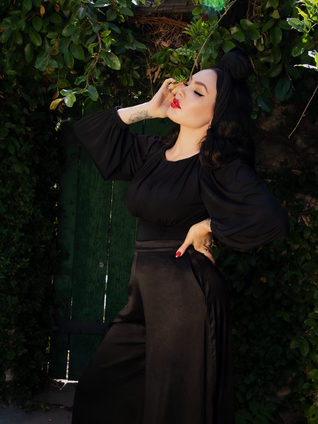 Micheline Pitt standing in an all-black gothic style outfit from La Femme en Noir.