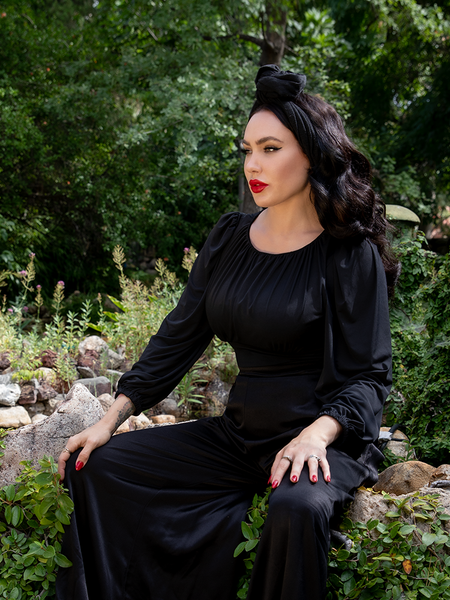 Micheline Pitt sitting on a stone bench covered in green moss while modeling the Salem Top in Black.
