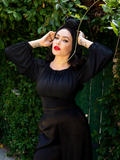 Micheline Pitt posing in her garden with an all gothic retro outfit including the Salem Top in Black.