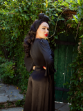 Micheline Pitt turned away from the camera while turning her head to look back while modeling the Salem Top in Black.