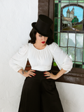 Micheline Pitt wearing the Salem Top in Ivory paired with black loose fitting pants and black tophat.