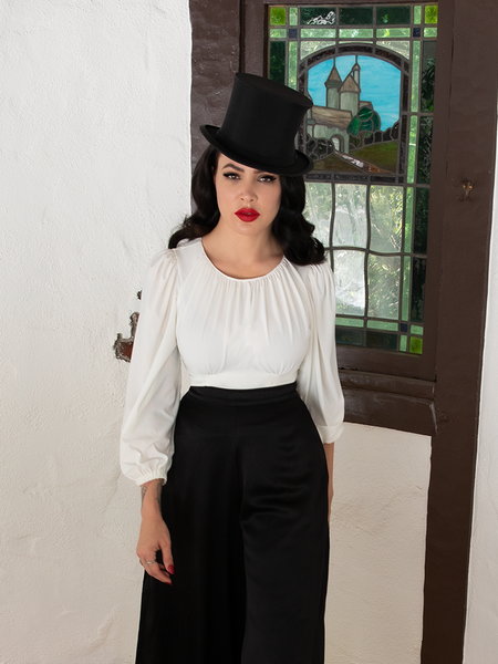 Micheline Pitt staring directly into the camera mid-strut while wearing the Salem Top in Ivory.