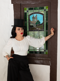 Micheline Pitt wearing a black tophat, white flowy top and loose black pants standing in front of a stained glass window.